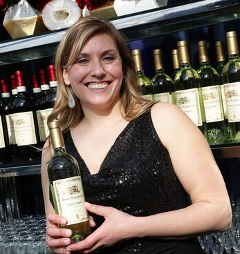 girl smiling in black dress while standing and holding a bottle of white wine