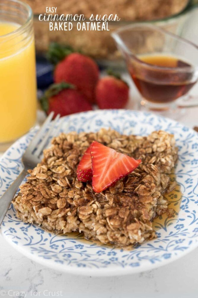 This Cinnamon Sugar Baked Oatmeal on blue plate with fork, strawberries, syrup and title