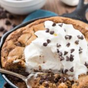 skillet chocolate chip cookie with chocolate chips and whipped cream on top and title text in top right corner