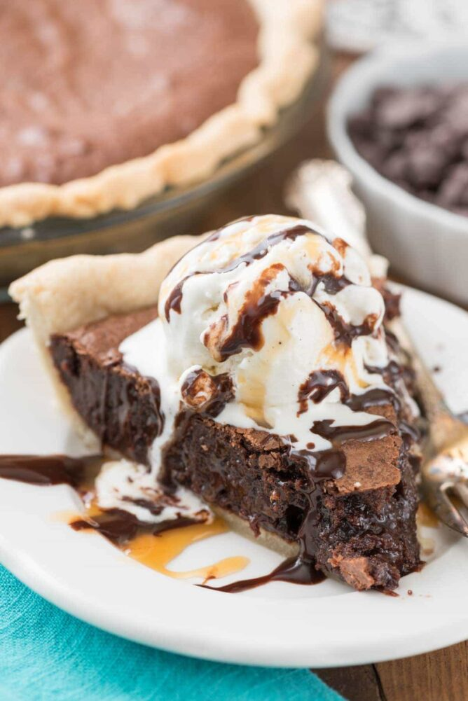 Slice of brownie pie on plate topped with ice cream and hot fudge