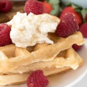 Stack of cheesecake waffles with whipped cream and raspberries
