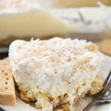 Slice of coconut cheesecake no bake dessert on white plate with fork