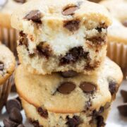 Stack of two cream cheese filled chocolate chip muffins with top muffin cut in half to show cream cheese