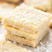 Close up shot of three gooey coconut pie bars stacked on eachother