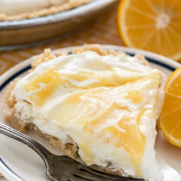 Slice of no bake lemon cheesecake on plate with fork and half a lemon