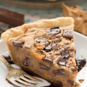Slice of peanut butter candy bar pie on white plate with silver fork