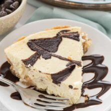 Slice of chocolate swirl cheesecake pie on white plate with silver fork