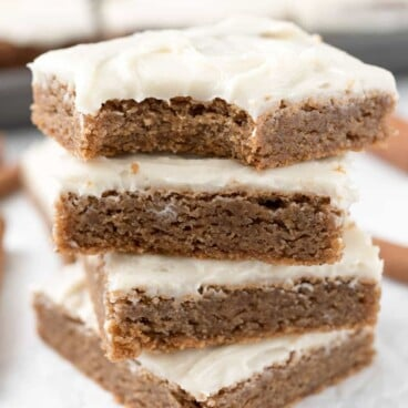 Stack of four cinnamon roll blondies with top one missing a bite