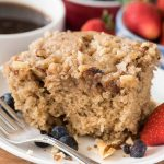 Slice of slow cooker coffee cake on white plate with strawberries and blueberries