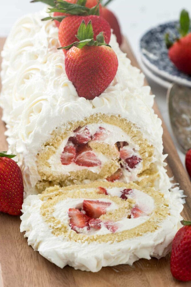 vanilla cake roll filled with strawberries and whipped cream frosting on cutting board