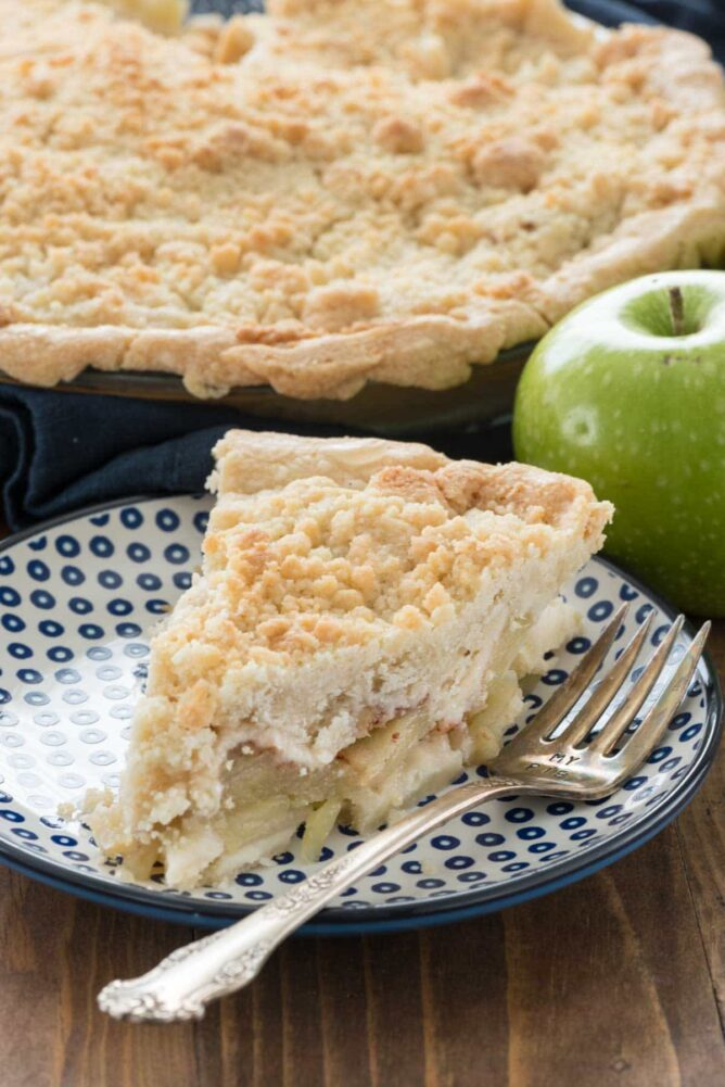 Slice of dutch apple pie on a plate with a fork.
