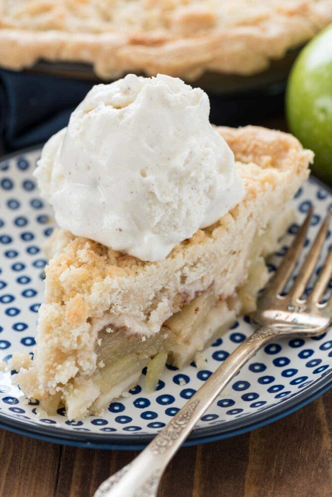 Slice of Apple pie with ice cream sitting on a blue and white plate with a fork