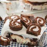 Piece of swiss roll layered no bake dessert on blue and white plate