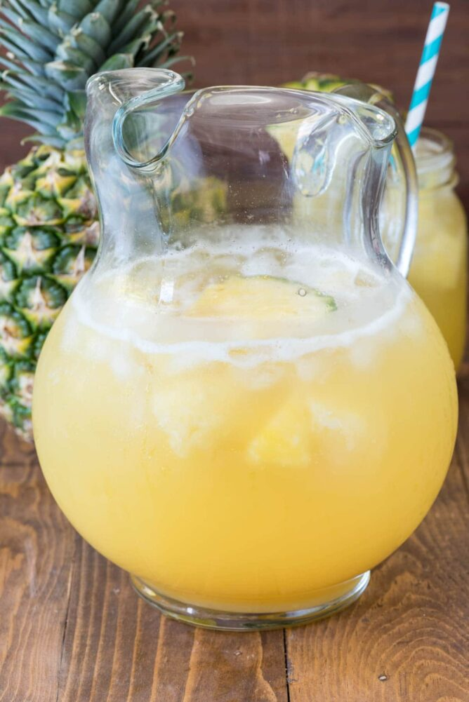 Pineapple party punch in a glass pitcher with a pineapple behind and a glass of punch with a straw