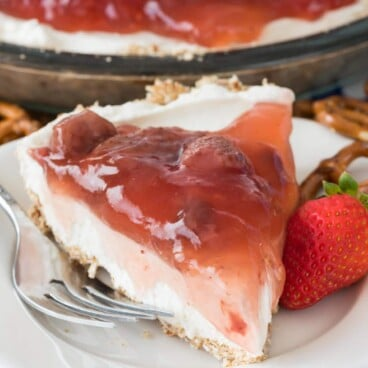 Slice of strawberry pretzel salad pie on white plate with full pie in the background