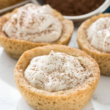 Three tiramisu cookie cups with cocoa in background
