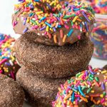 Stack of three perfectly baked chocolate donuts with rainbow sprinkles on top