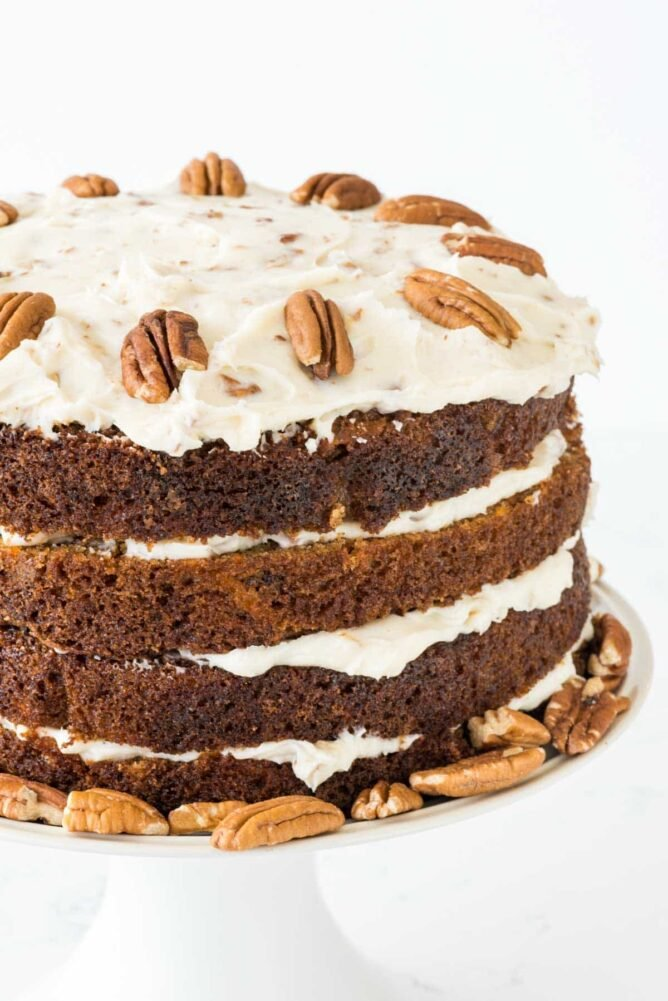naked carrot cake with frosting between layers and pecans on top