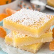 Stack of three orange dream bars with powdered sugar on top
