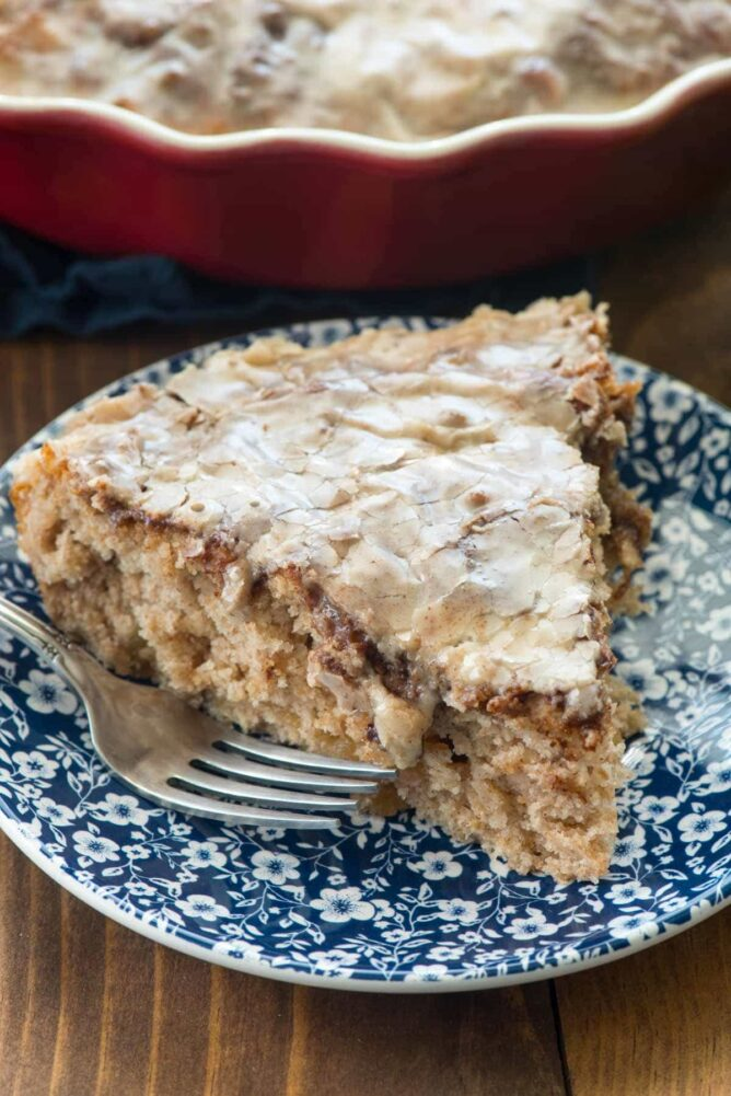 Slice of Apple Fritter Cake on a blue and white plate with a fork