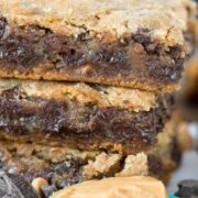 Stack of double decker gooey cookie bars with spoonful of peanut butter in front