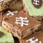 Chocolate chip cookie cake pieces with frosting and football decor
