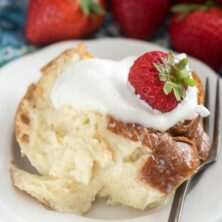 Piece of tres leches french toast casserole on white plate with fork