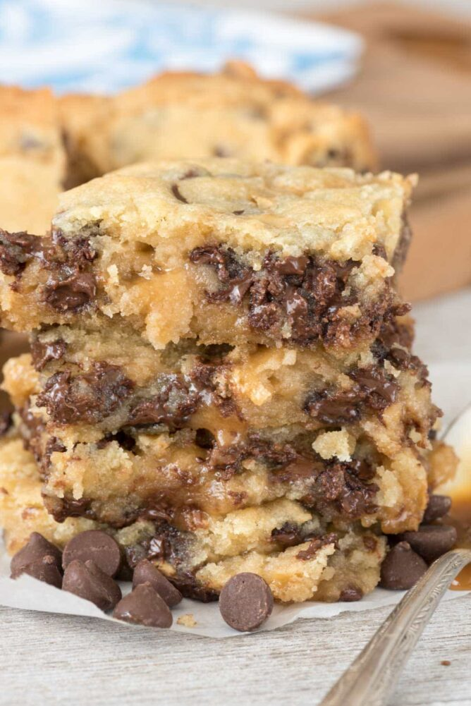 Chocolate Chip Caramel Gooey bars stacked on parchment paper
