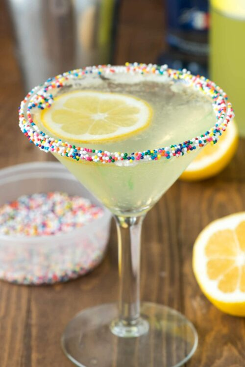 Lemon cupcake martini in a martini glass with sprinkles and lemon slices