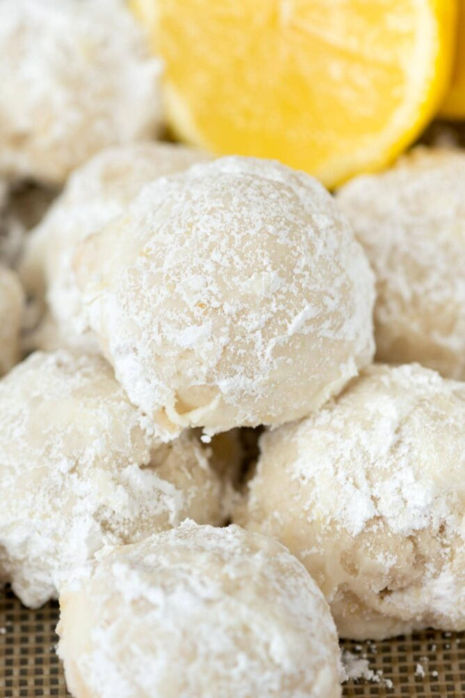 Buttery Lemon Snowball Cookies with a lemon in the background
