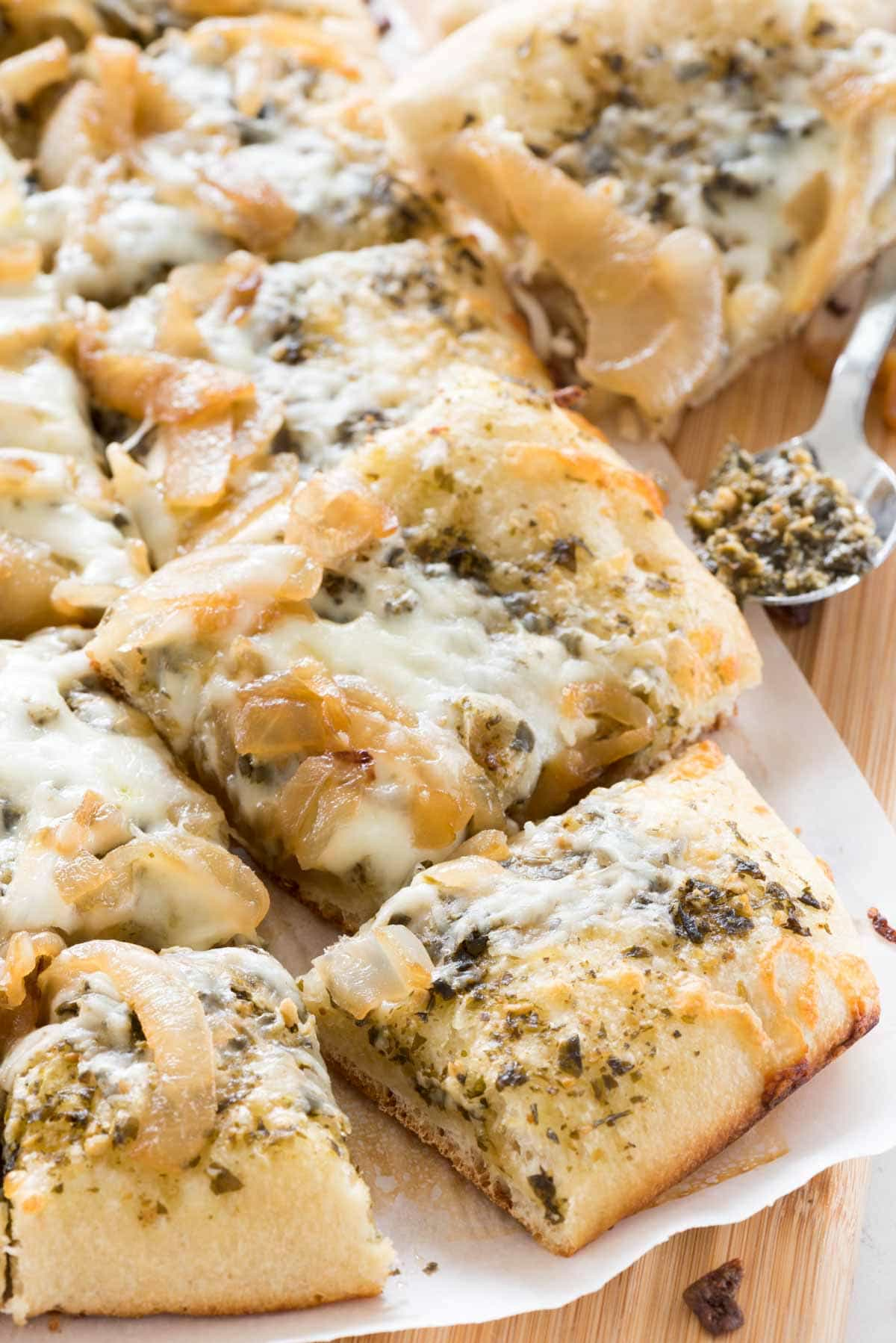Caramelized Onion Pesto Flatbread Pizza - this EASY 4 ingredient pizza recipe is the perfect appetizer. Pesto, caramelized onions, and mozzarella baked onto a pizza crust - every time I make this people rave about it!