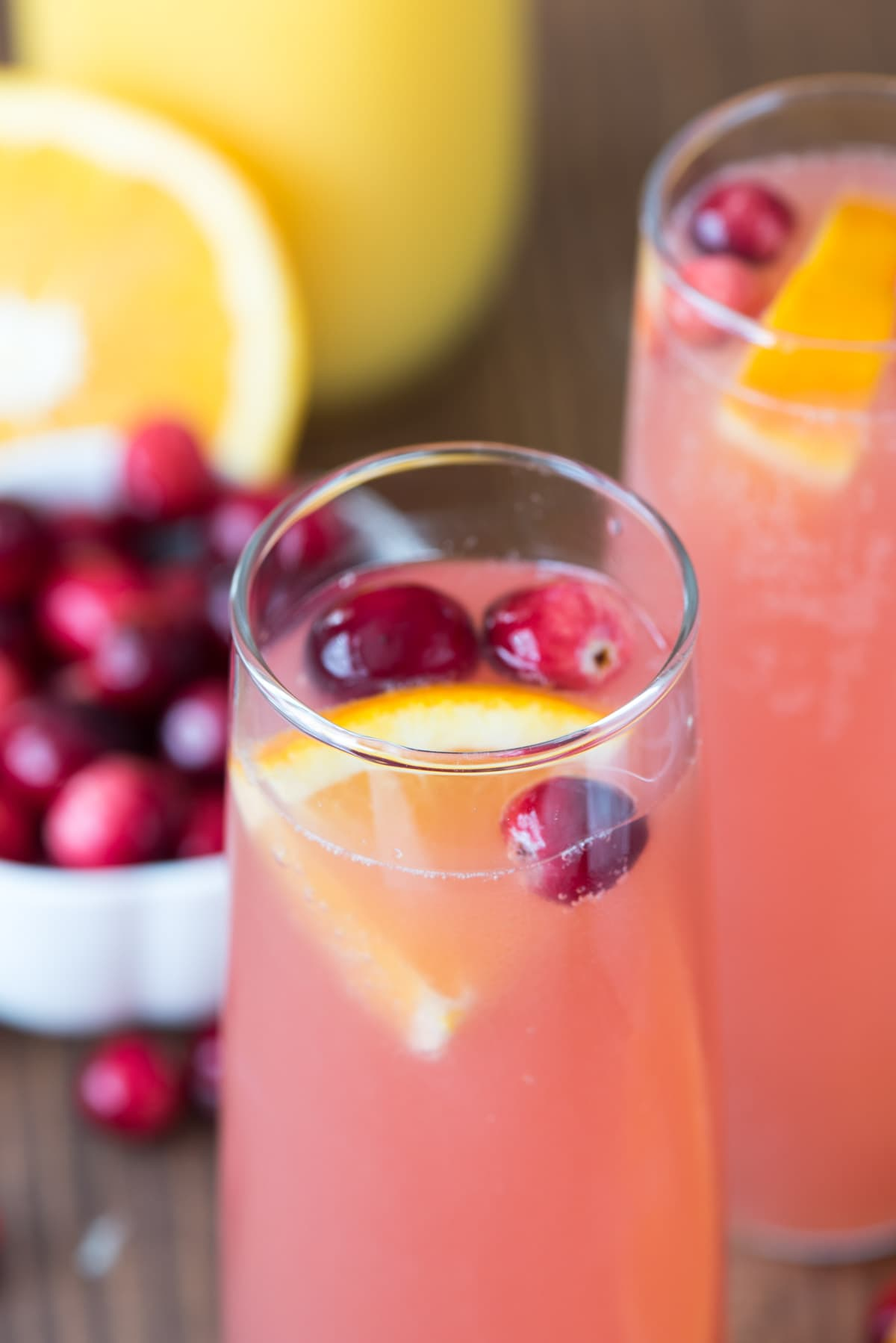 Two Cranberry Orange Bellini Mimosas garnished with cherries and sliced oranges.