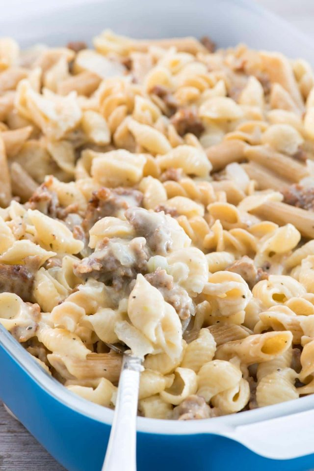 Scooping Sausage Mac & Cheese out of a blue casserole dish.