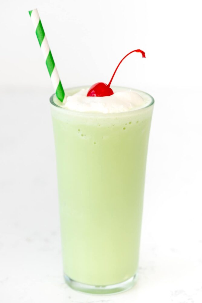 Copycat Mint Shamrock Shake in tall glass with a straw and a cherry