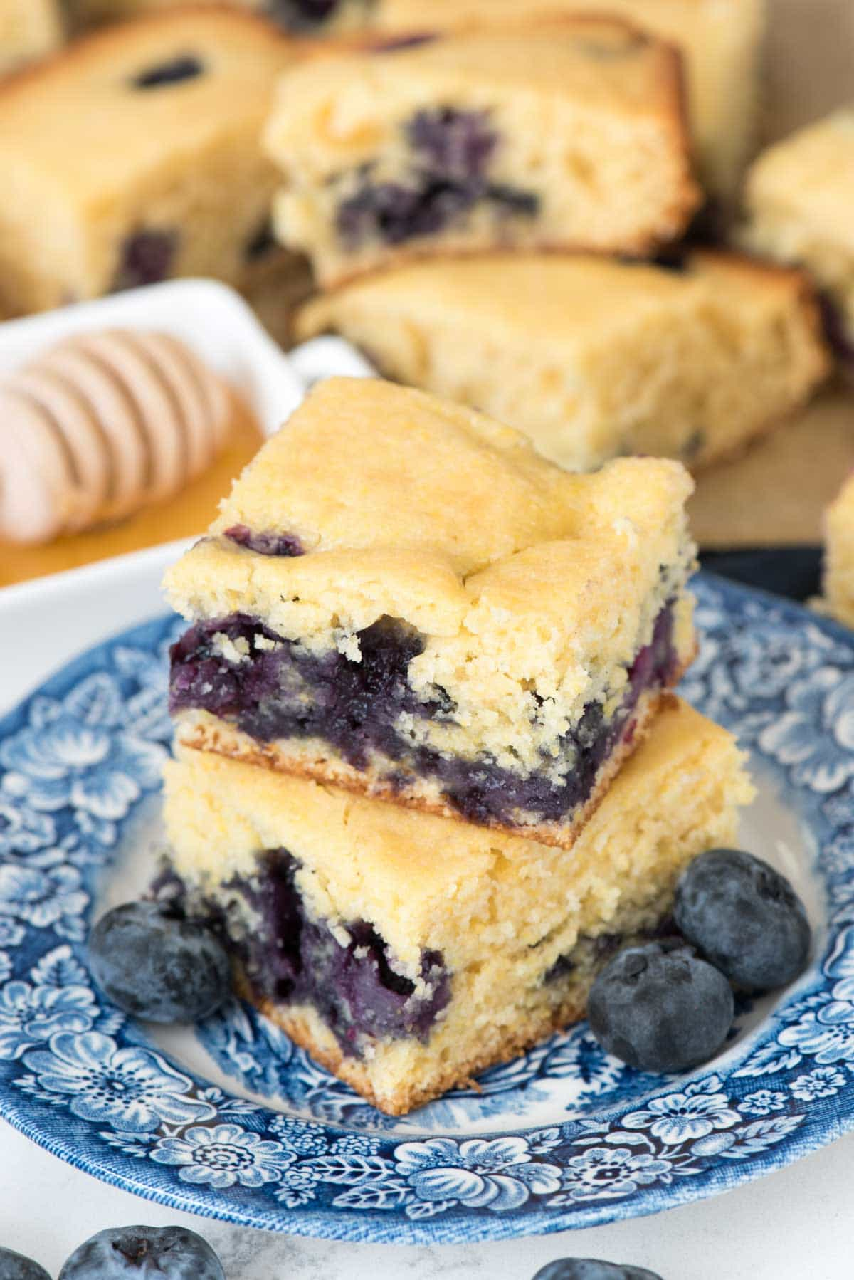 Blueberry Cornbread on a blue serving plate with blueberries on the side.