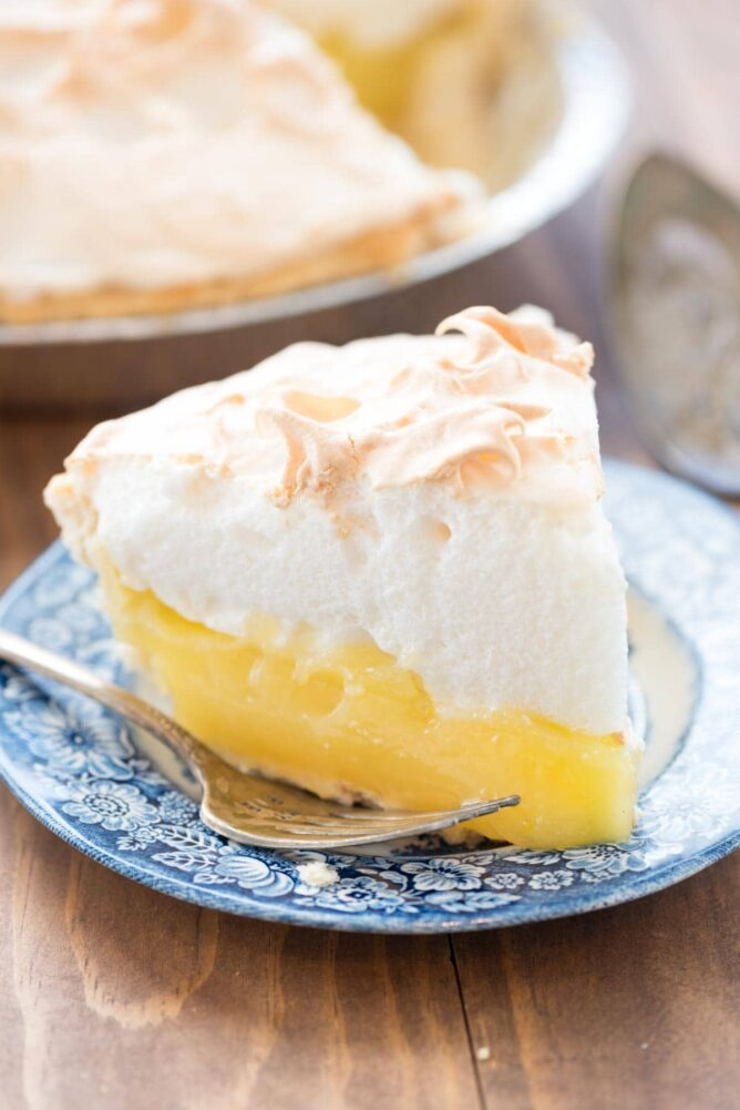 Aunt Tootsie's Lemon Meringue Pie on a blue plate with a fork.