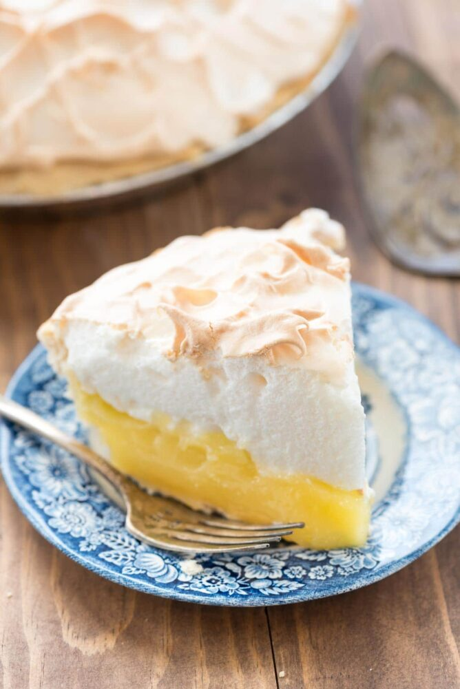 Slice of Aunt Tootsie's lemon meringue pie on a blue plate with fork
