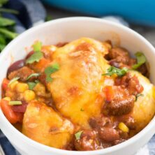 Easy Cheesy Chili Biscuit Bakein a white bowl - this easy weeknight dinner recipe has just 5 ingredients! Chili is topped with vegetables, biscuits, and cheese then baked up for a delicious comfort food meal.
