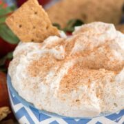 Churro Cheesecake Dip in a bowl with graham crackers to dip - an easy way to make no-bake cheesecake dip full of cinnamon sugar churro flavor! This is the perfect party dip or an easy dessert recipe.