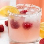 Raspberry Lemonade Margarita on a white counter - this EASY cocktail recipe is the perfect margarita! Raspberry Lemonade, tequila, and triple sec- that's all it takes to make a pitcher!