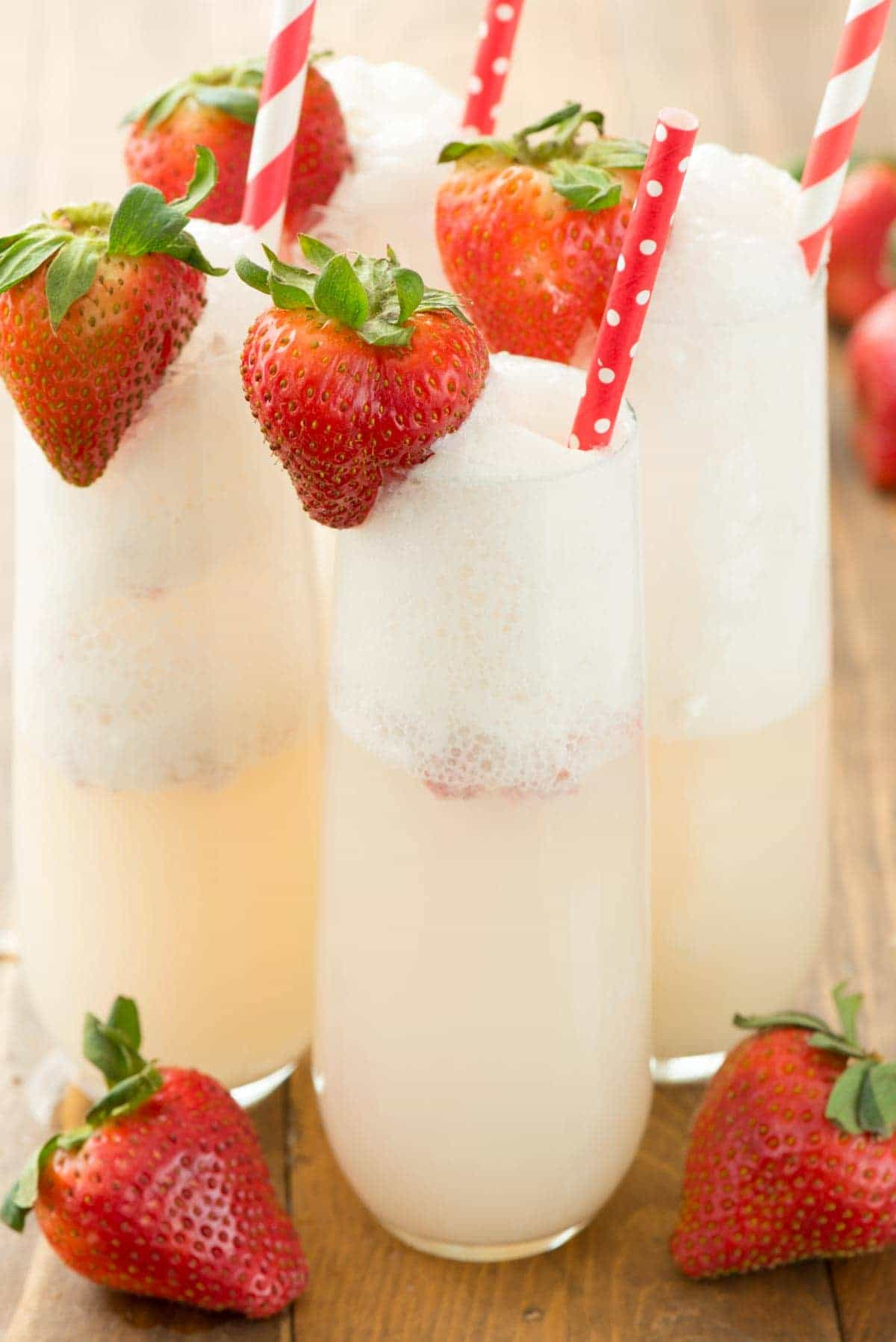 Four Strawberry Shortcake Mimosa with straws garnished with fresh strawberries.