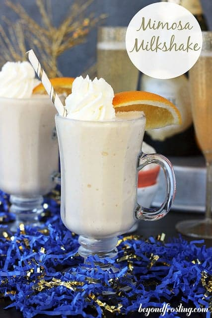 Two Mimosa Milkshakes with straws garnished with whipped cream and sliced oranges.