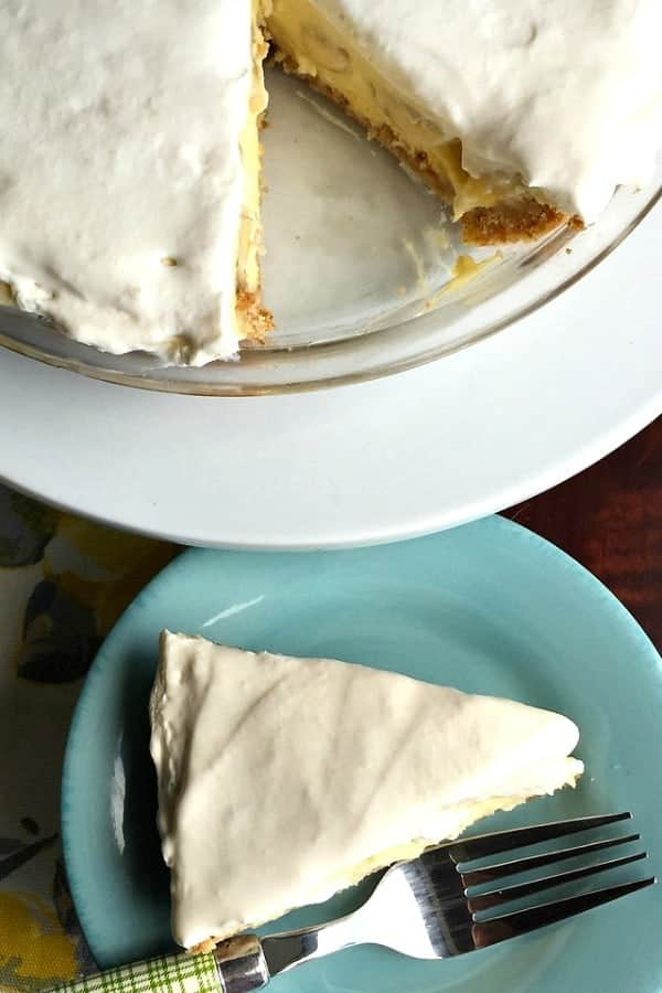 Slice of Banana Cream Pie with a silver fork on a teal serving plate.