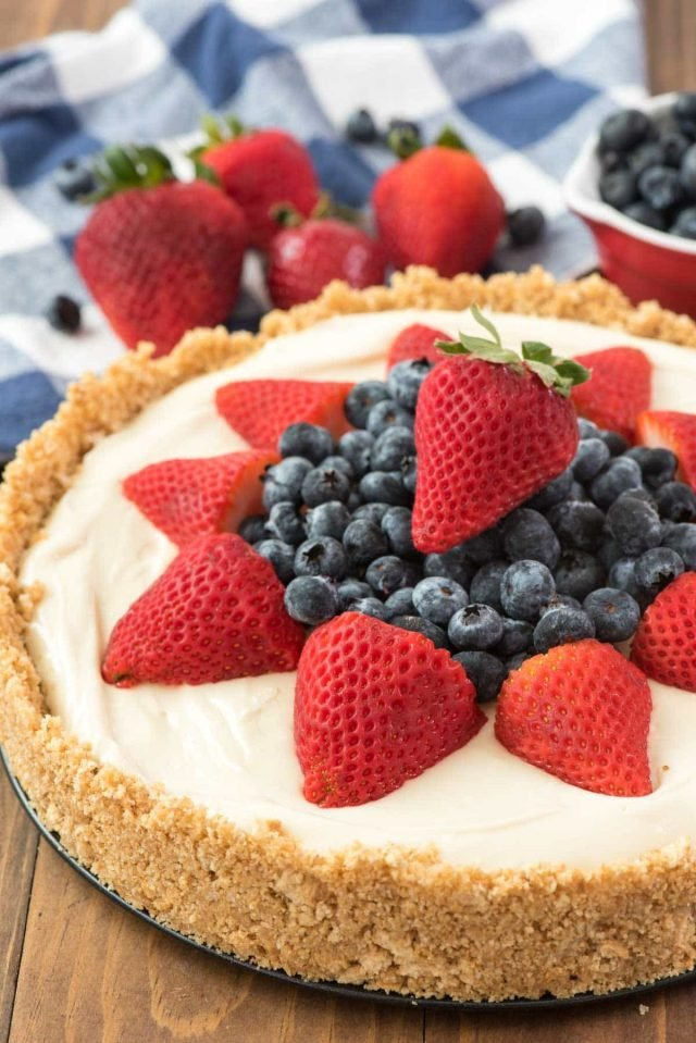 BEST NO BAKE CHEESECAKE RECIPE EVER topped with blueberries and strawberries on a wooden board.