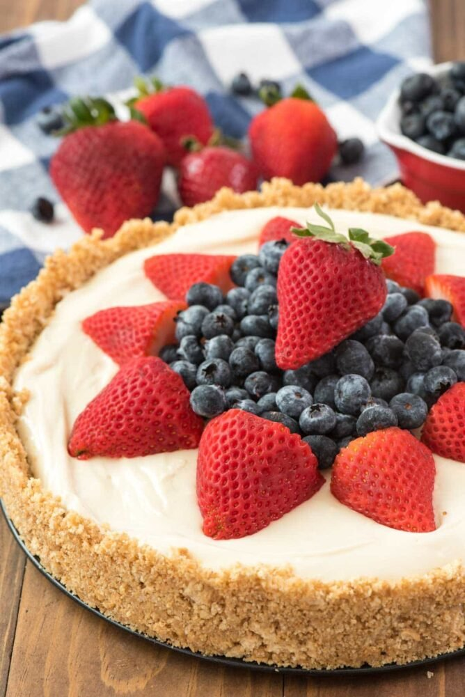 THE BEST NO BAKE CHEESECAKE RECIPE topped with strawberries and blueberries on a wooden board.