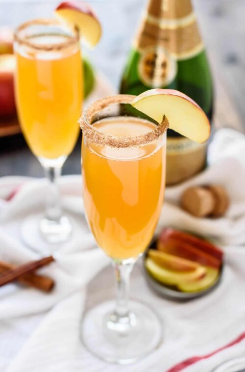 Two champagne cocktails with apple slices and a bottle of champagne