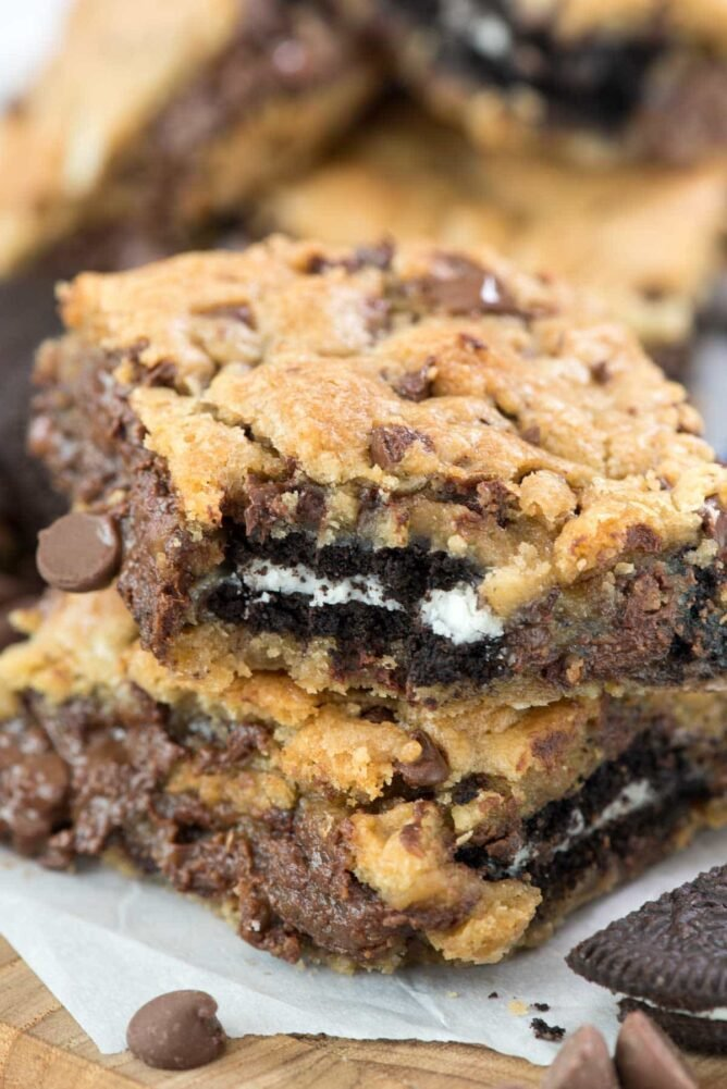 Oreo Stuffed Chocolate Chip Cookie Gooey Bars in a stack with bite missing