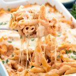 Easy Baked Penne Pasta Casserole in a blue casserole dish and a fork full being lifted out of the dish