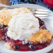 Easy Cherry Berry Dump Cake on a white plate with a fork