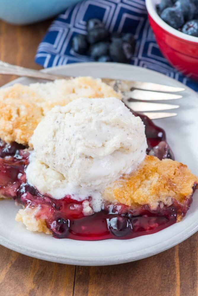 cherry berry dump cake with ice cream on top on white plate with fork and berries behind